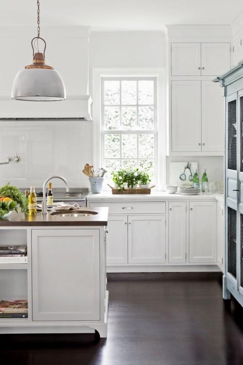 Gemütliche Küche ganz in weiß visueller Kontrast dunkler Holzboden grüne Akzente