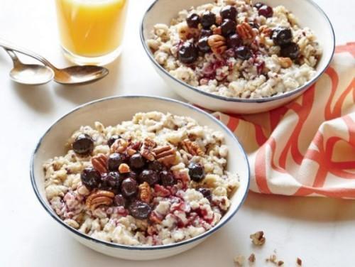 Gesunde Lebensmittel morgens eine Schüssel Haferflocken essen mit Beeren und Nüssen