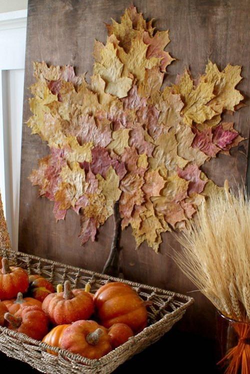 Herbstdeko basteln bunte Herbstblätter an der Wand schön arrangiert Zierkürbisse Weizenstängel darunter