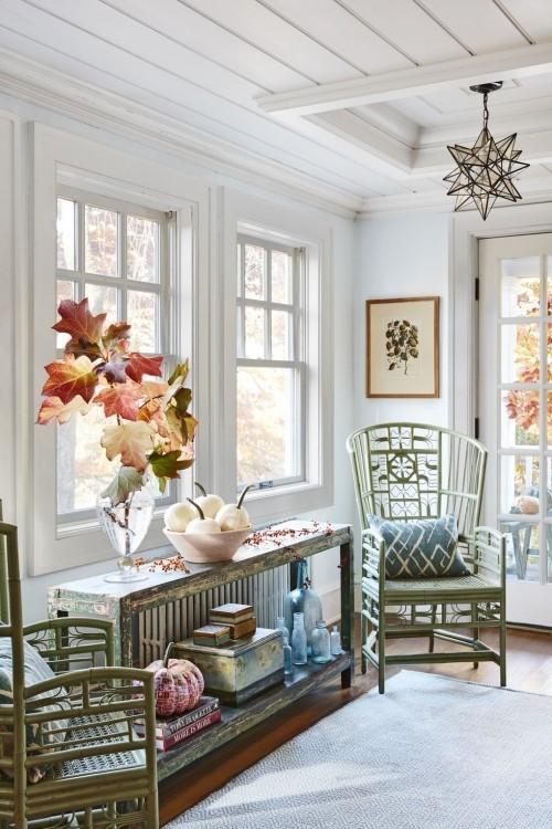 Herbstdeko basteln warme Farben ins Interieur bringen Vase mit großen Herbstblätter Kürbisse