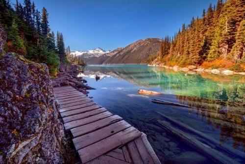 Kanada bereisen Holzbrücke Blick auf Gletschersee Kieferwald naheliegende Berge