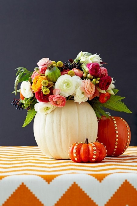 Ausgehöhlte Kürbisse als Vasen voll mit Herbstblumen Tischdeko im Herbst