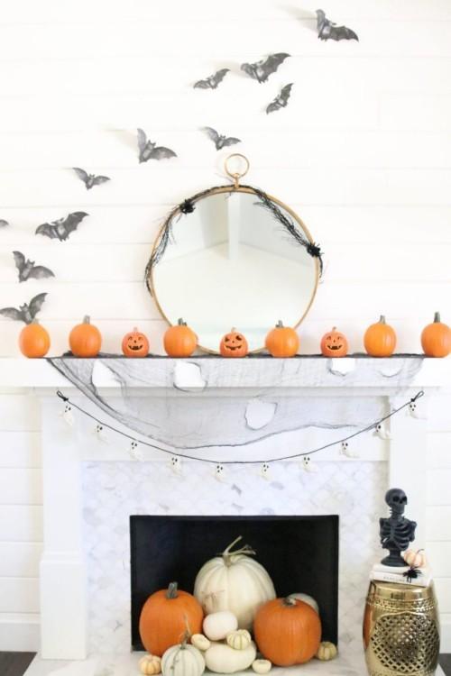 Deko Ideen zu Halloween den Kaminsims dekorieren Kürbisse schwarze Federmäuse