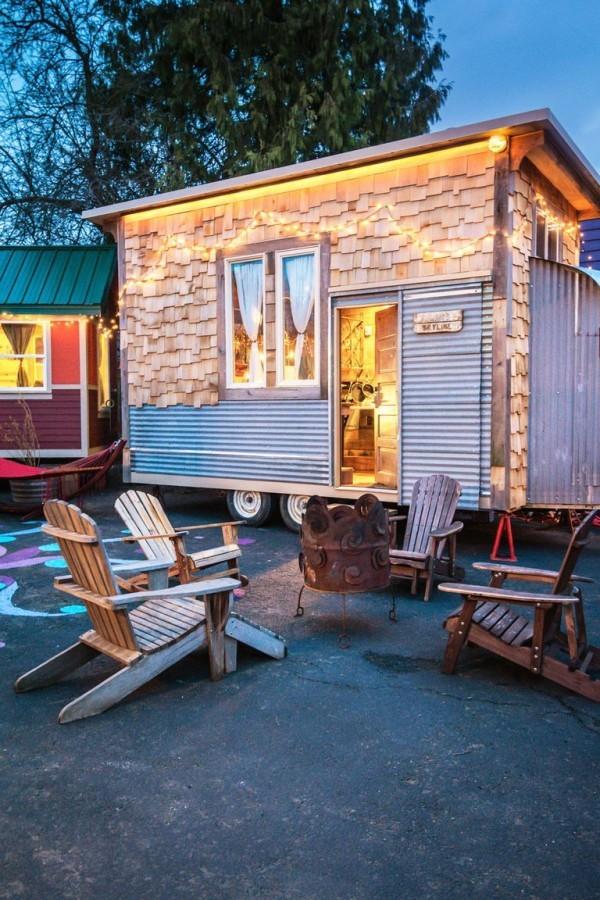 Tiny Houses ein kleines Haus aus Metall und Holz auf Rädern mit Sitzecke im Freien