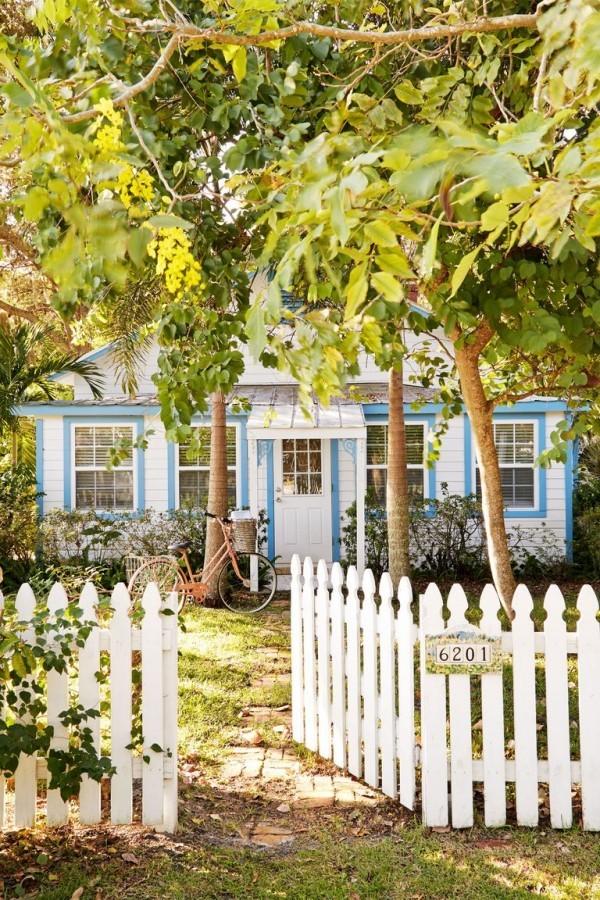 Tiny Houses kleines Haus mit Garten Holzzaun weiß viele Bäume