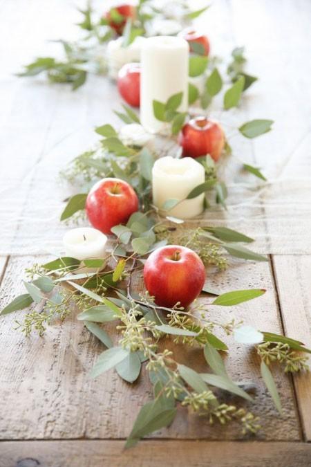 Tischdeko im Herbst rote Äpfel Kerzen grüne Blätter