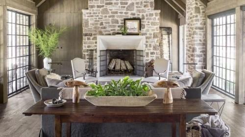 Wohnzimmer im Landhausstil gedeckte Farben bequeme Möbel Holztisch im Vordergrund Steinwand Kamin