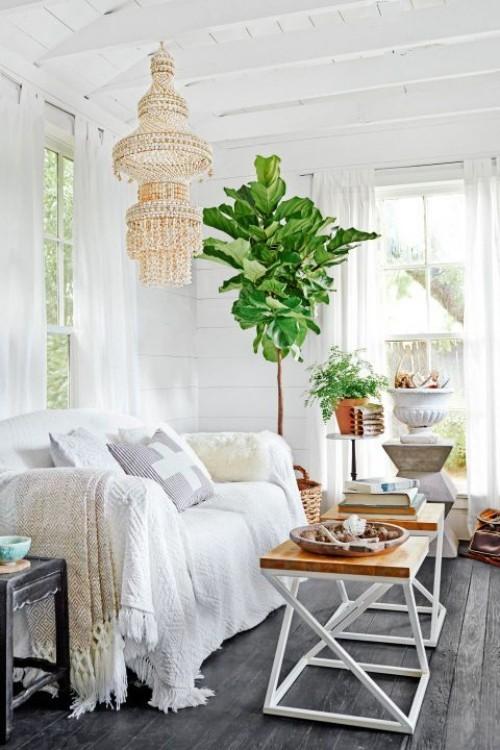 Wohnzimmer im Landhausstil weiße Couch Zimmerpflanzen alter Kronleuchter Klapptische