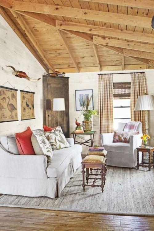 Wohnzimmer im Landhausstil weiße Möbel Zimmerdecke aus Holz bunte Kissen