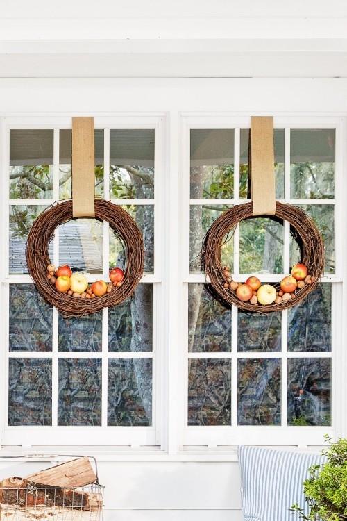 Zwei Herbstkränze am Fenster zur Veranda Äpfel Nüsse verflochtene Zweige