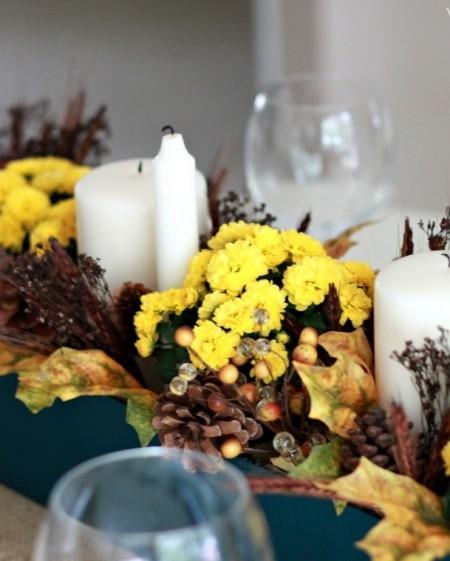 gelbe Chrysanthemen weiße Kerzen Tannenzapfen Tischdeko im Herbst