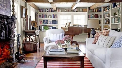 gemütliches Wohnzimmer im Landhausstil viel Holz weiße Möbel gestreifter Teppich Balken Bücherwand