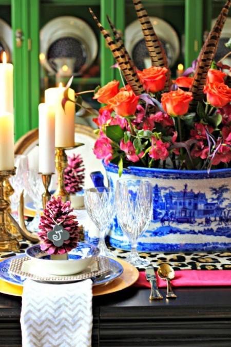 schönes Arrangement Blumen federn Kerzen Tannenzapfen Tischdeko