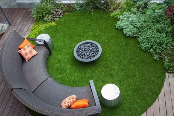 schicke Gestaltung runde Feuerstelle im Zentrum halbrundes Sofa bunte Kissen als Akzente