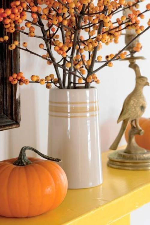 tolle Deko Ideen zu Halloween den Kaminsims dekorieren Kürbis Hagebutten Vogelfigur orange gelb beige