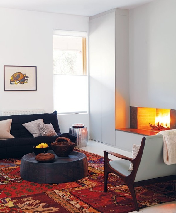 Gemütlichkeit zuhause ockerfarbener roter Teppich mit Ethno-Mustern eleganter Kamin