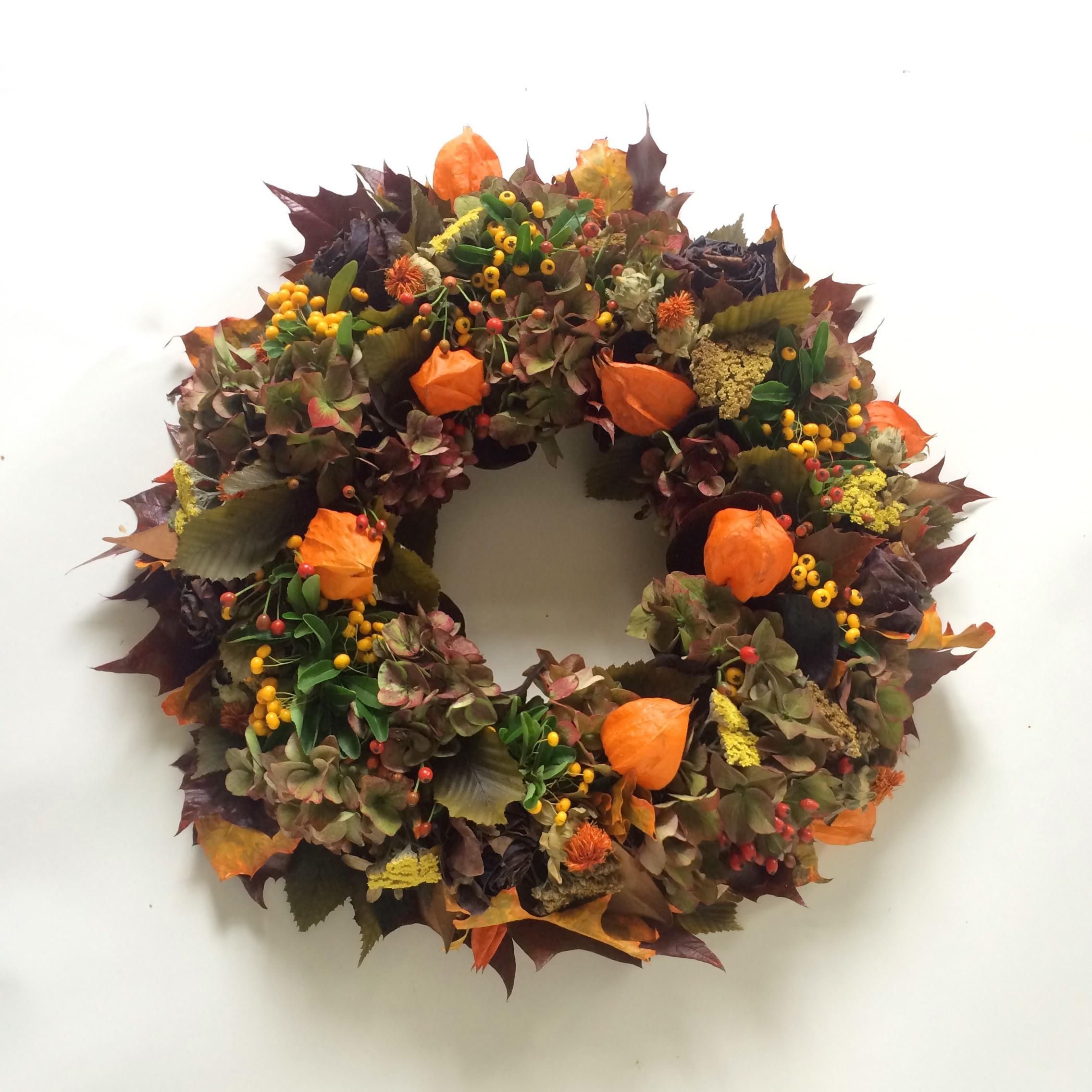 Herbstkränze in Grün mit verschiedenen orangen Akzenten