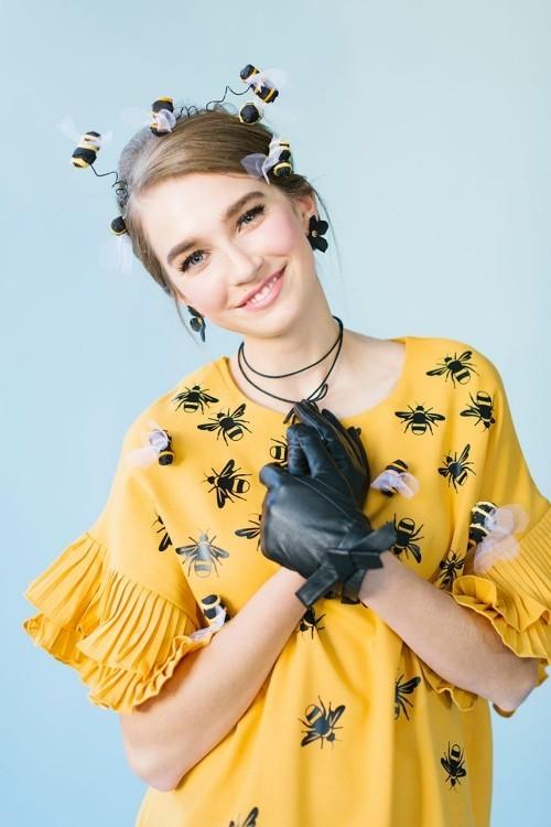 Lustige Halloween Kostüme als eine Biene gelbes Kleid gemustert mit schwarzen Handschuhen