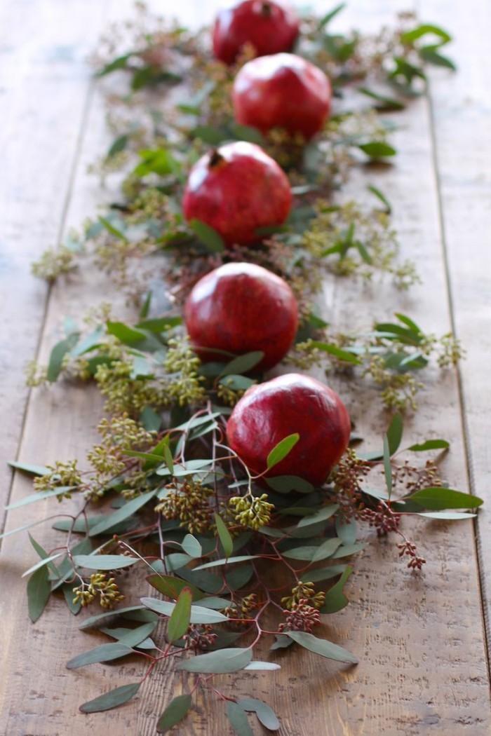 Tischdeko Ideen zu Weihnachten Granatäpfel und grüne Blätter zum Dekorieren