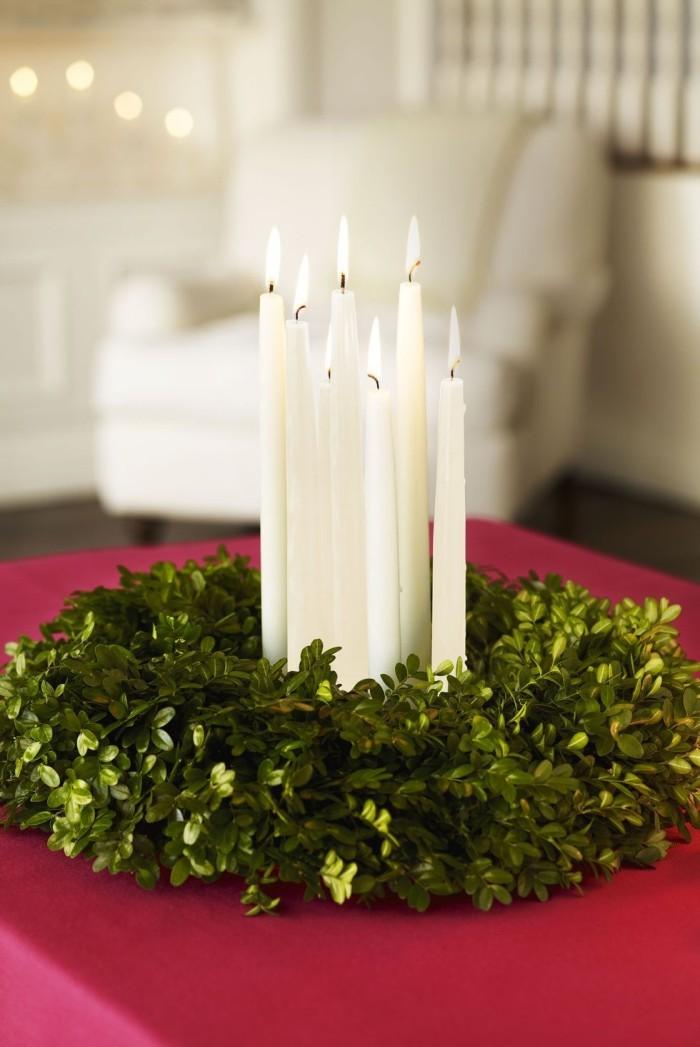 Tischdeko Ideen zu Weihnachten Kranz binden aus grünen Efeuzweigen brennende weiße Kerzen