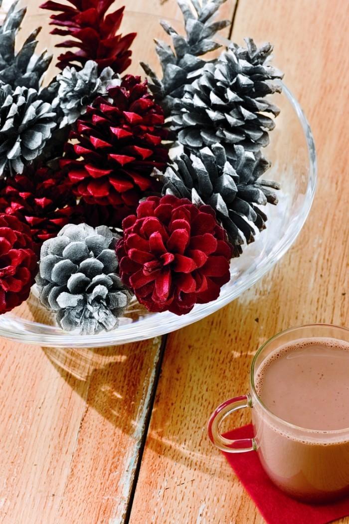 Tischdeko Ideen zu Weihnachten Zapfen in verschiedenen Farben bemalt in einer Schüssel zentral arrangiert Tasse heißer Kakao