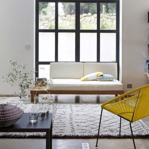modernes Wohnzimmer viel Tageslicht Zweisitzer vor dem Fenster Blumen grauer Teppich