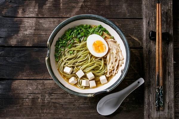 Japanisches Essen Suppe mit Nudeln Frühlingsgemüse Pilze gekochtes Ei mit Stäbchen und weißem Löffel serviert