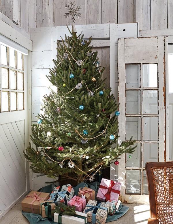 Weihnachten auf dem Lande feiern Christbaum in der Ecke schön geschmückt darunter Geschenk