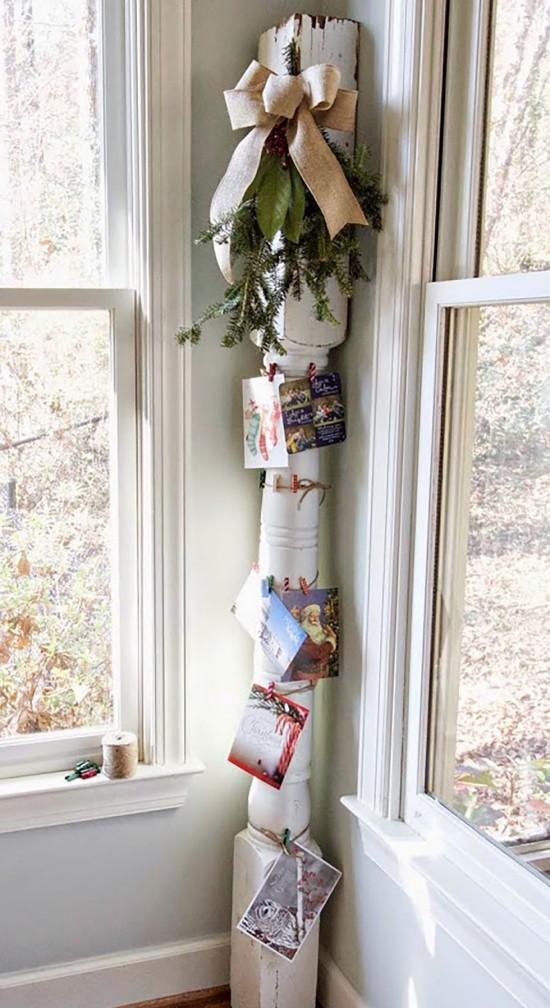 Weihnachtskarten an einer Holzsäule anbringen Tannengrün und Schleife dazu