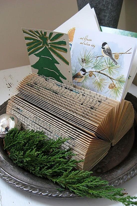 Weihnachtskarten zwischen Buchseiten halten