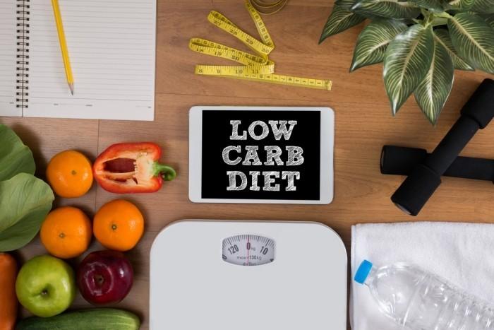Essen ohne Kohlenhydrate Low Carb Diät Waage Flasche Mineralwasser frisches Obst Gemüse