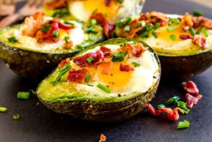 Essen ohne Kohlenhydrate das perfekte Frühstück halbierte Avocado mit Ei und Speck überbacken