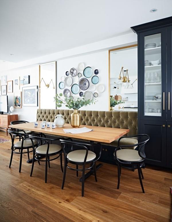 Frühstücksecken olivgrünes Sofa elegante Stühle großer Frühstückstisch Wandteller Kollektion Vase mit Blumen