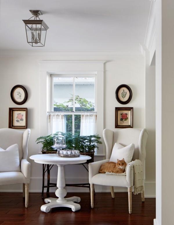 Frühstücksecken sehr gemütlich gestaltet weiße Polstersessel kleiner Tisch Bilder Topfblumen Katze