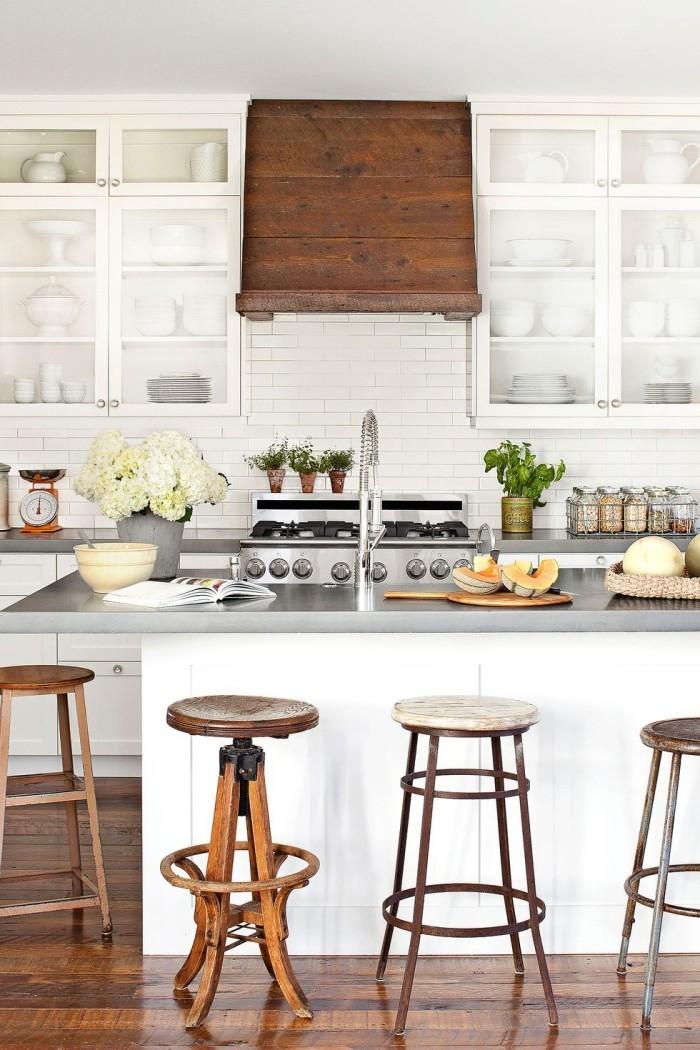 Kücheninsel Alt trifft Neu moderne Arbeitsplatte mit Metallglanz alte Hocker im Retro-Look
