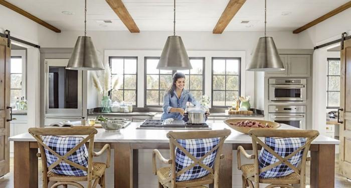Kücheninsel breite Arbeitsplatte Metallakzente oben Hängeleuchten drei bequeme Stühle