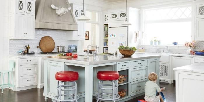 Kücheninsel breite Arbeitsplatte viel Stauraum zwei rote Hocker Sitzgelegenheit