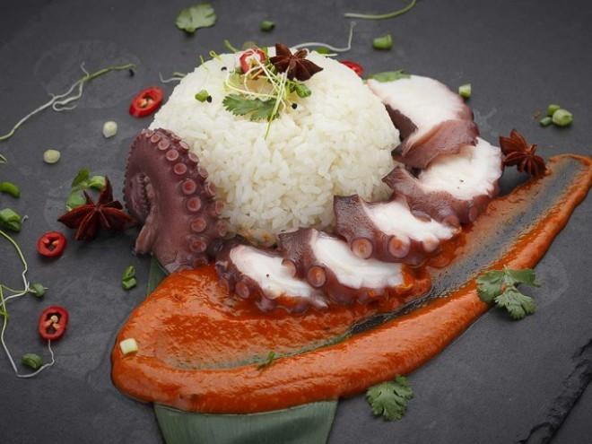 Reiseziele 2019 typisches Essen auf den Seychellen Oktopus mit Reis und Curry Sauce auf Steinplatte serviert