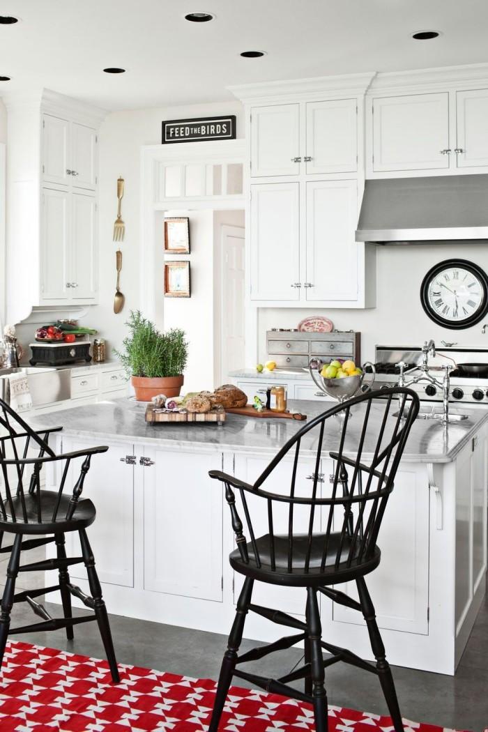 weiße Kücheninsel zwei schwarze Stühle roter Teppich als Akzente