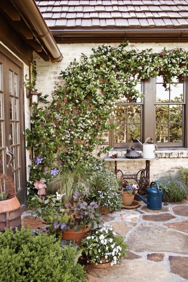 Gartengestaltung Ideen Steinplatten vor dem Hauseingang Kletterpflanzen Topfpflanzen schöner Blick