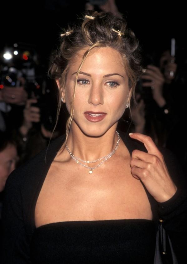 Jennifer Aniston im offiziellen Outfit mit hochgestecktem Haar und Haarklammern in Schmetterlingsform
