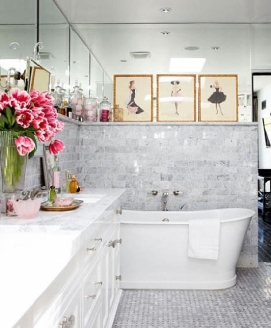 Badezimmer mit weiblichem Gespür helles Interieur weiße Badewanne Waschtisch Blumen Bilder
