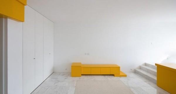 Kleine Wohnung minimalistisches Raumkonzept wenige Möbel gelbe Akzente