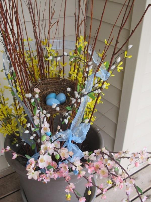 Osterdeko draußen Eimer mit blühenden zweigen Nest mit blau gefärbten Eiern