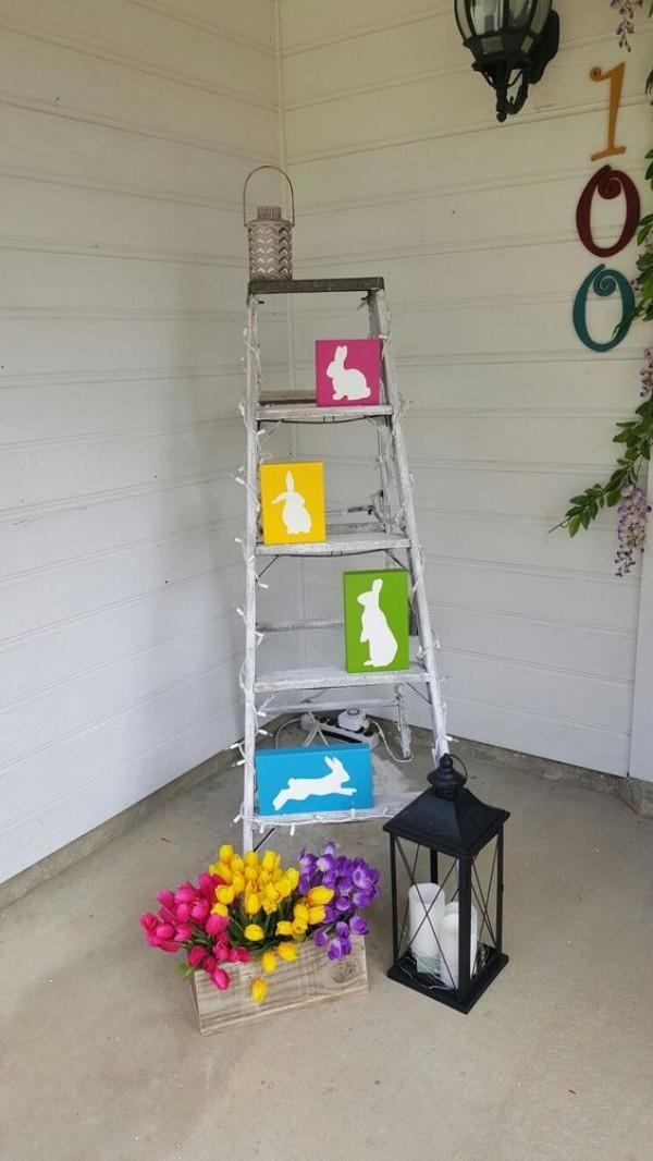Osterdeko draußen Hasenzeichnungen Leiter Kasten mit Tulpen Laterne mit weißen Kerzen