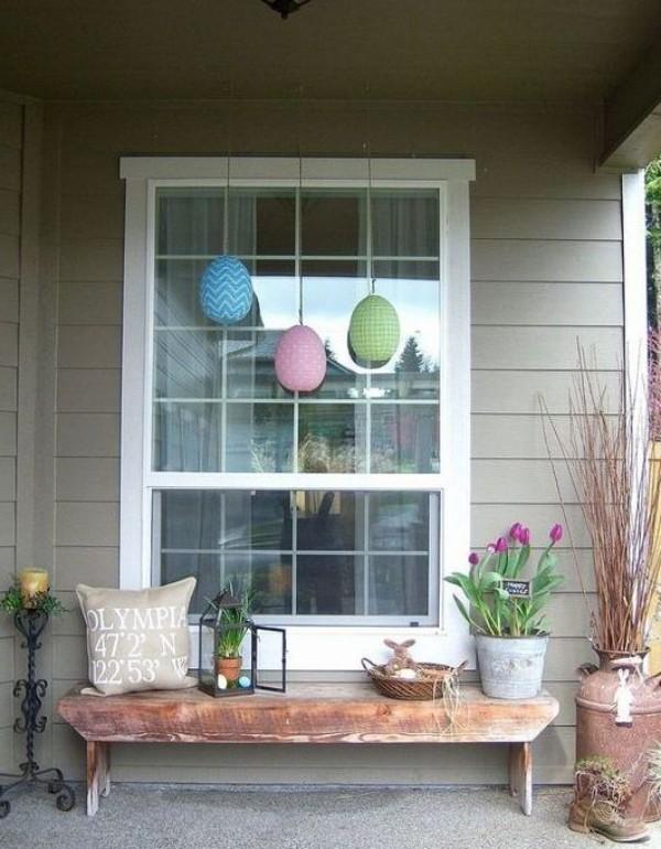 Osterdeko draußen Sitzbank auf der Veranda Blumen drei große bunte Eier hängen