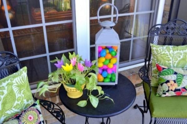 Osterdeko draußen Terrasse dekorieren bunte Sitzkissen Laterne mit bunten Eiern Topf mit Grünpflanze und Blumen darin