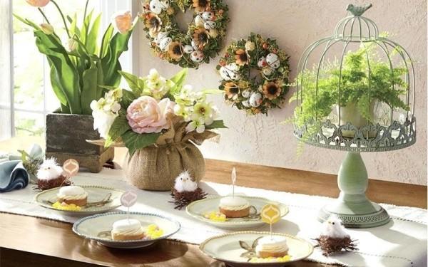 Osterdeko draußen festlich dekorierter Tisch zum Kaffeetrinken Blumen zwei Kränze