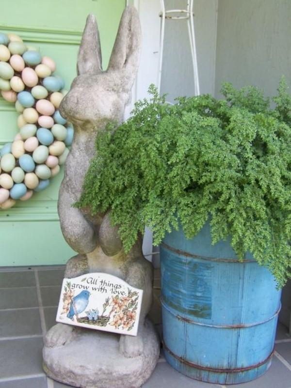 Osterdeko draußen großer Hase aus Stein oder Beton Grünpflanze Kranz aus Ostereiern