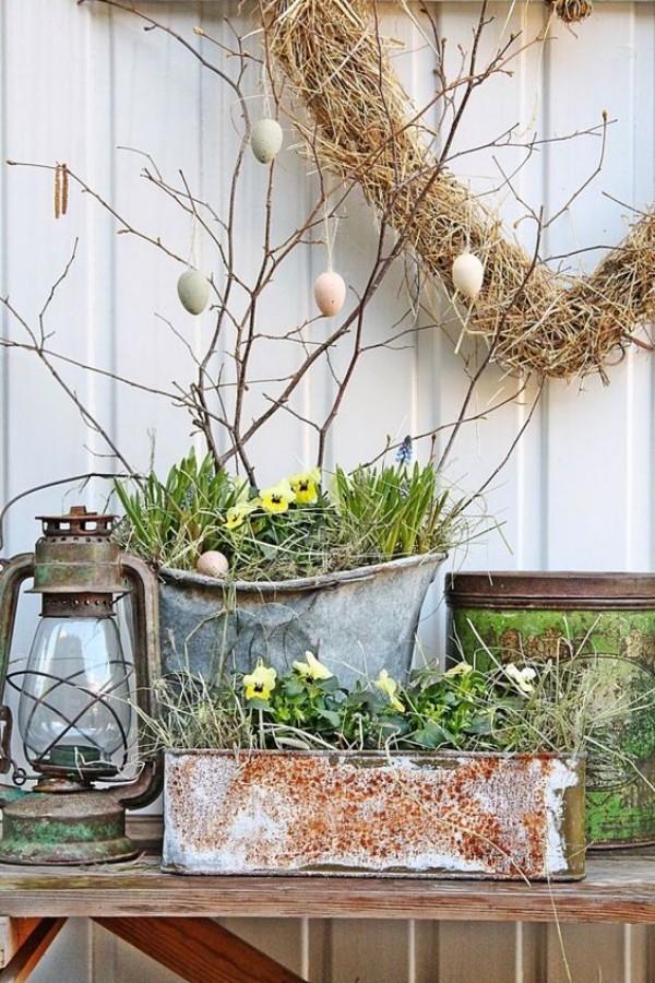 Osterdeko draußen in Vintage Stil alte Metallbehälter mit Stiefmütterchen Laterne Kranz mit Ostereiern